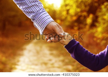 the parent holds the hand of a small child - stock photo