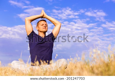 The peaceful scenery of a man meditating in the lotus position. - stock photo
