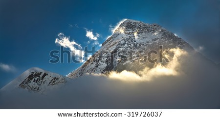 The peak of the highest mountain in the world - Mt. Everest in the light of the first sunrays. - stock photo