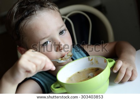 The pensive child eating soup at home - stock photo