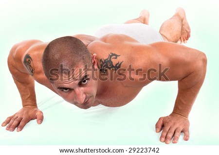 The perfect muscular male doing push-ups - stock photo