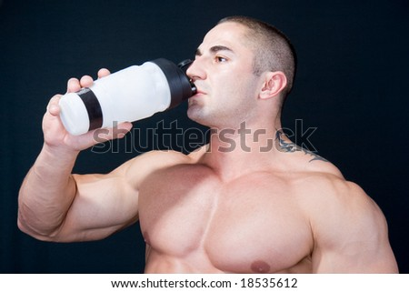 The Perfect  muscular man enjoying a bottle of water after exercise - stock photo