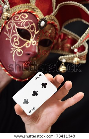 The person in a mask with cards. - stock photo