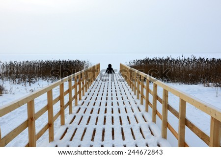The person sits on the embankment in the winter - stock photo