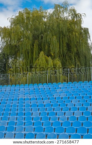 The photographic image of plastic folding chairs on sports arena. - stock photo