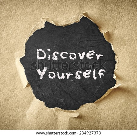 the phrase discover yourself written over chalkboard through torn paper  - stock photo