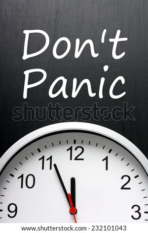 The phrase Don't Panic written on a blackboard above a clock with the time set at five minutes to or almost midnight or high noon - stock photo