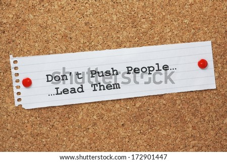 The phrase Don't push People, Lead Them on a paper note pinned to a cork notice board. A concept for leadership being used to motivate people. - stock photo