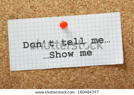 The phrase Don't Tell Me, Show Me typed on a piece of graph paper and pinned to a cork notice board. Often used in business but more so as a guide for novel and book writers. - stock photo