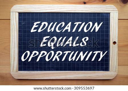 The phrase Education Equals Opportunity in white text on a slate blackboard as a reminder that qualifications lead to work - stock photo