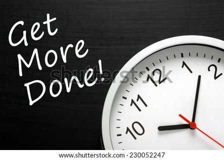 The phrase Get More Done written on a blackboard next to a modern office wall clock. A Time Management concept - stock photo