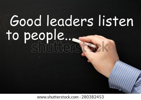 The phrase Good Leaders Listen to People in white text on a blackboard as a reminder of leadership skills - stock photo