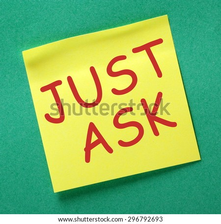 The phrase Just Ask in red text on a yellow sticky note posted on a green notice board as a reminder - stock photo
