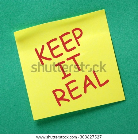 The phrase Keep It Real in red text on a yellow sticky note posted on a green notice board as a reminder - stock photo