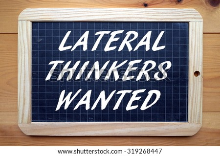 The phrase Lateral Thinkers Wanted in white text on a blackboard as a recruitment message for people who think outside the box - stock photo