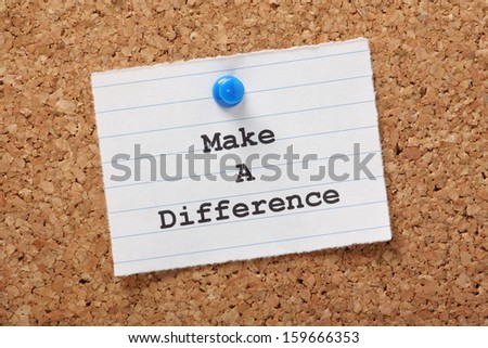 The phrase Make A Difference on a paper note pinned to a cork notice board. - stock photo