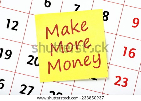 The phrase Make More Money on a yellow sticky note attached to a wall calendar as a reminder or resolution for next year - stock photo