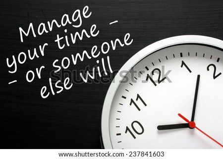 The phrase Manage your time - or someone else will, written on a blackboard next to a modern clock. - stock photo