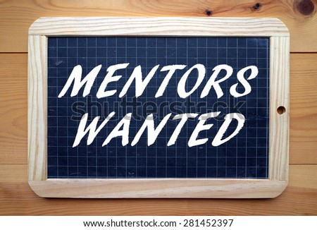 The phrase Mentors Wanted in white text on a slate blackboard placed flat on a wooden surface - stock photo