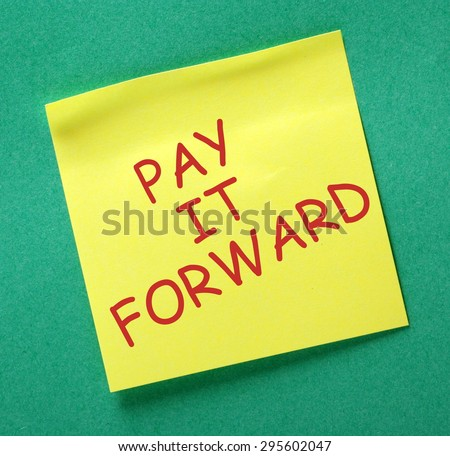 The phrase Pay It Forward in red text on a yellow sticky note posted on a green notice board - stock photo