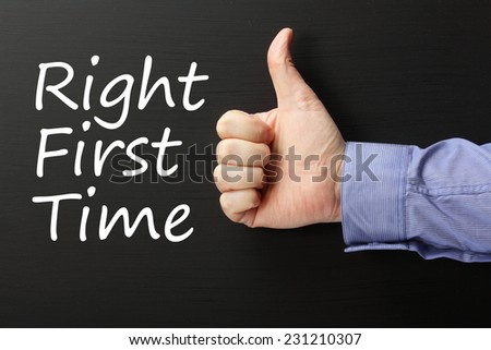 The phrase Right First Time on a blackboard with a male hand in a business shirt giving the thumbs up sign. Right First Time is a term used in Quality Control Improvement - stock photo