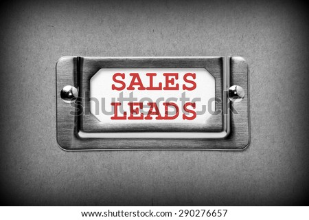 The phrase Sales Leads in red ink on the label in a storage box card holder. Image processed in black and white with a vignette for effect - stock photo