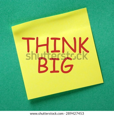 The phrase Think Big in red text on a yellow sticky note posted on a green notice board as a reminder  - stock photo