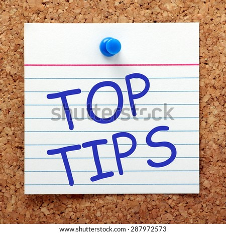 The phrase Top Tips in blue text on an index card pinned to a cork notice board as a reminder - stock photo