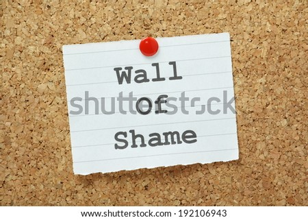 The phrase Wall of Shame typed on a piece of paper and pinned to a cork notice board - stock photo