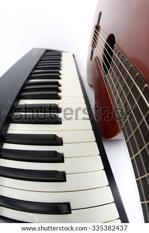 the piano keys and classical guitar close up on white background - stock photo