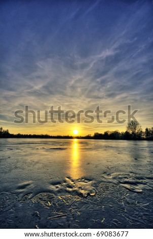 The picture shows a frozen lake at sunset. - stock photo