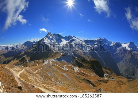 The picture was taken Fisheye lens. Austrian Alps. Excursion to the picturesque panoramic way Grossgloknershtrasse. Sunny day in early autumn. Great highway winds between hillsides yellowed - stock photo