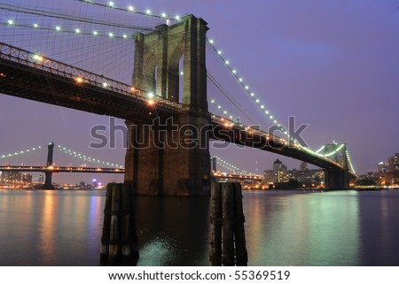 The Picturesque Brooklyn Bridge shimmering at night as it spans the east river in New York City. - stock photo