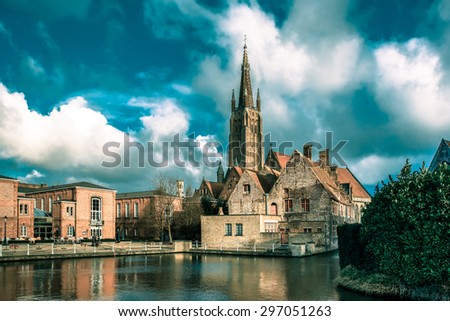 The picturesque city landscape with a lake, Old St Johns Hospital and the Church of Our Lady in Bruges, Belgium. Toning in cool tones - stock photo