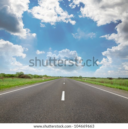 The picturesque country road in the background of the relief of the sky. - stock photo