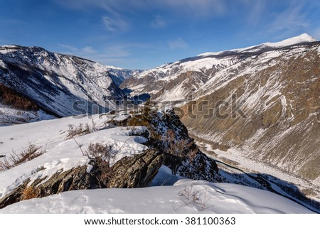 The picturesque top view on the mountains covered with snow, cliffs and the valley between the mountains in the canyon on a background of blue sky and clouds in winter - stock photo