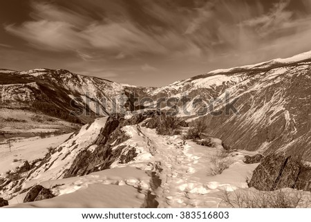 The picturesque top view on the mountains covered with snow, cliffs and the valley between the mountains on a background of sky and clouds in winter - stock photo