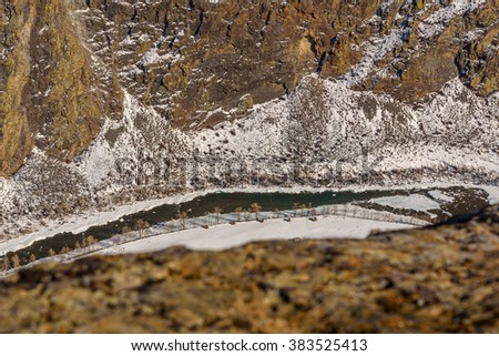 The picturesque top view on the river with the transparent water, houses and trees in the valley between the mountains in winter - stock photo
