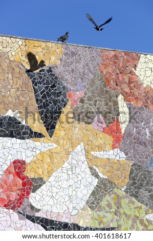 The pigeon flying over colorful wall of mosaic in the city of Seattle (Washington). - stock photo
