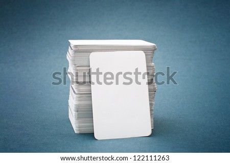 The pile of blank business cards lays propped up another business card. - stock photo