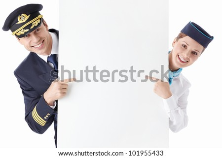 The pilot and flight attendant with a billboard - stock photo