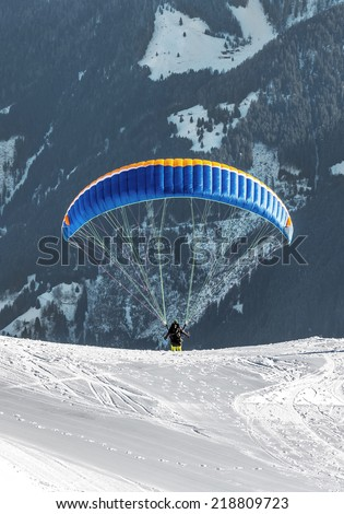 The pilot begins flight on a paraplane with a mountain-skiing slope of Penken - Mayrhofen, Austria - stock photo