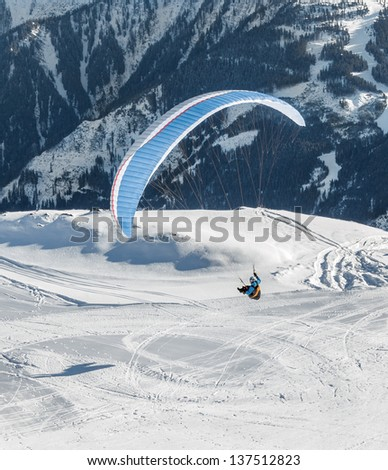 The pilot flies a paraglider with a mountain-skiing slope of Penken - Mayrhofen, Austria - stock photo