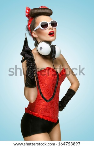 The pin-up photo of a cute girl in sunglasses with unplugged music headphones. - stock photo