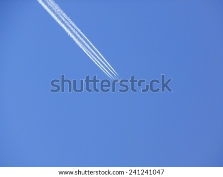 The plane in the blue sky. - stock photo