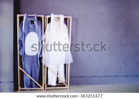 the play is over. costumes rabbits on a hanger. Suit gray rabbit and a white rabbit costume on brackets in the wardrobe of the theater. empty space for your text - stock photo