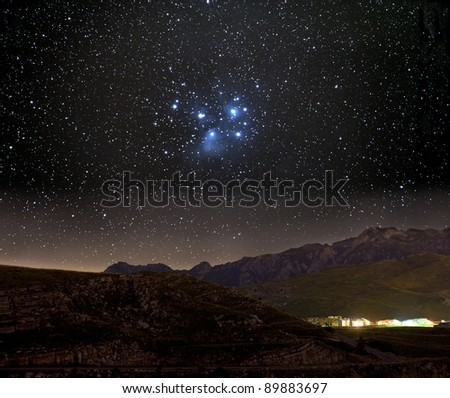 The Pleiades star cluster over a mountain village. - stock photo