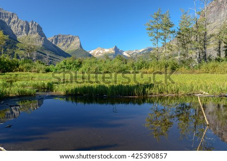 The pointed peak of Reynolds Mountain in the distance against a cloudless sky from an unnamed pond near St. Mary Lake, Glacier-Waterton International Peace Park, Montana, USA - stock photo