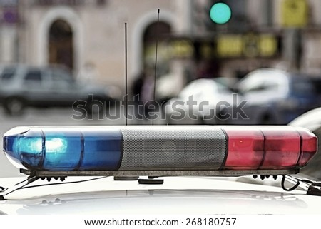 the police car provides control of a situation and patrol, the photo with a retro effect on indistinct a background of city streets and the motor transport - stock photo