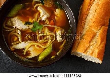 the popular comfort food of chicken noodle soup a favorite variety with crusty bread - stock photo